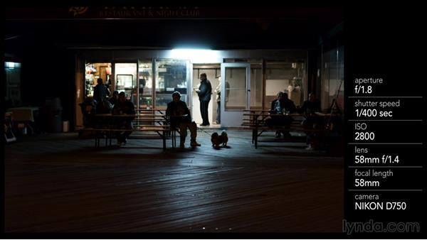 Shooting subjects in front of low-light boardwalk businesses: Street Photography: The City at Night
